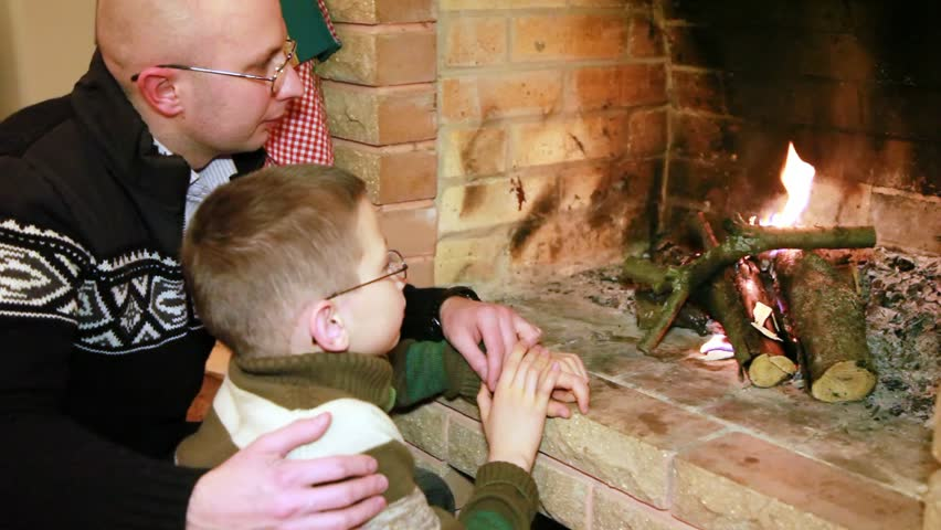 father and son in glasses sitting near fireplace and watch fire - HD stock footage clip
