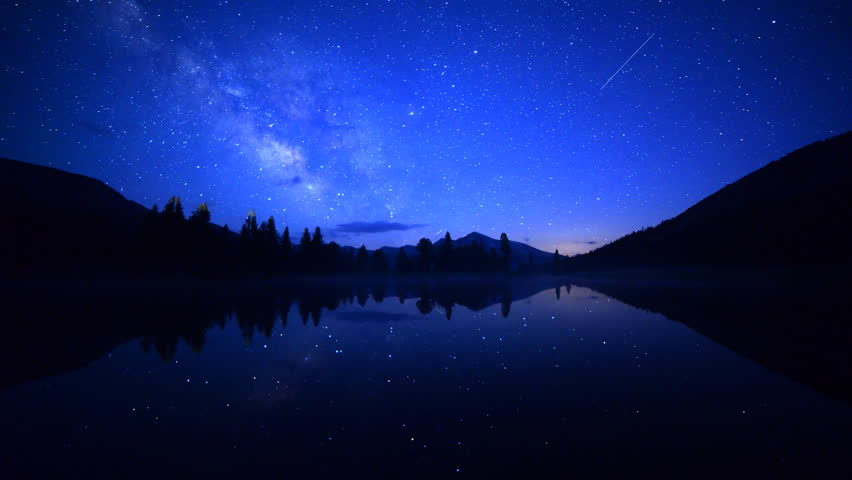 Astrophotography Time-lapse footage with zoom in motion of milky way galaxy spanning over reflective alpine lake in Yosemite National Park, California