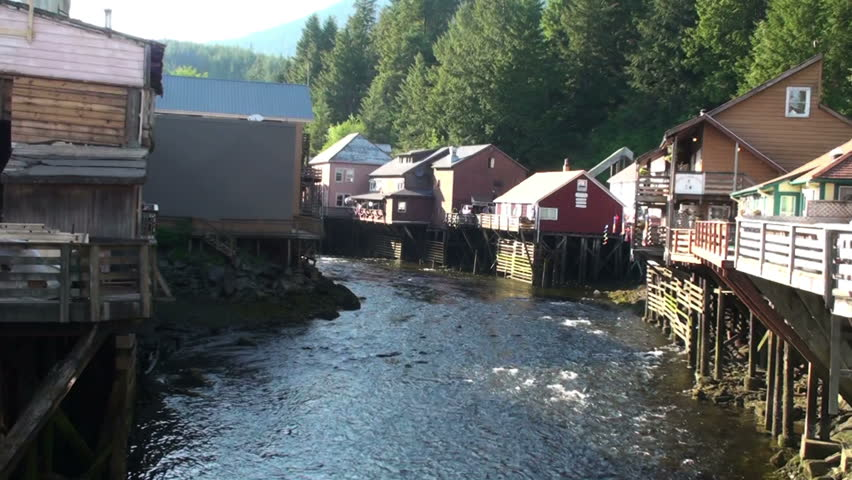 A steady shot of Ketchikan Creek and the adjoining Creek Street on a sunny day in Alaska. Houses built on wooden pilings as well as some trees in the background visible. Captured on June 5, 2009.