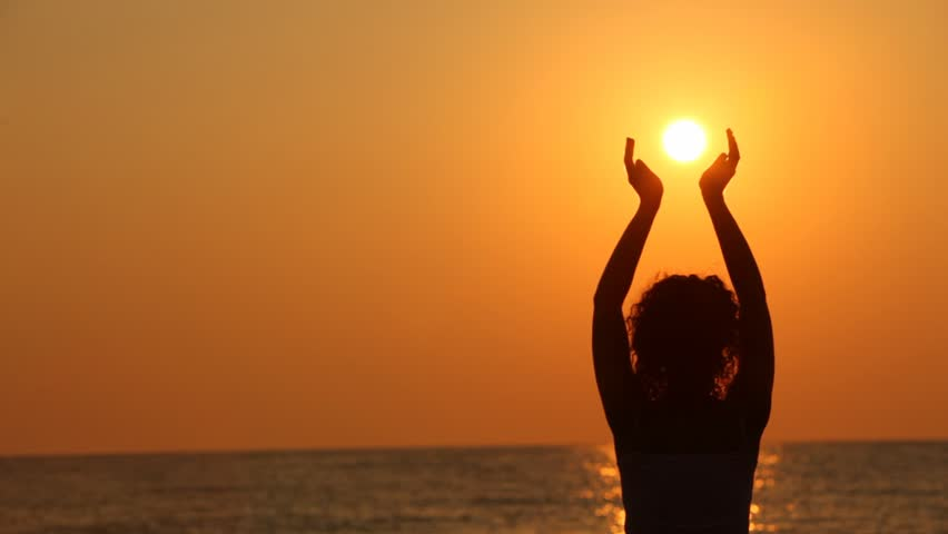 curly-headed woman standing on beach, watching sunset, holding sun in her hands - HD stock footage clip