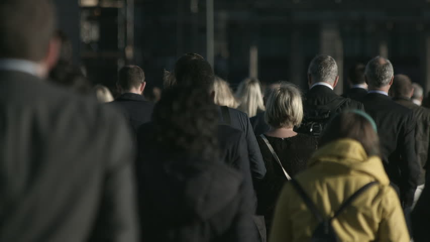 Large crowd of anonymous people in front of grey building in 4K. Large crowd of commuters and pedestrians walk across London Bridge to the City of London on a sunny morning in September