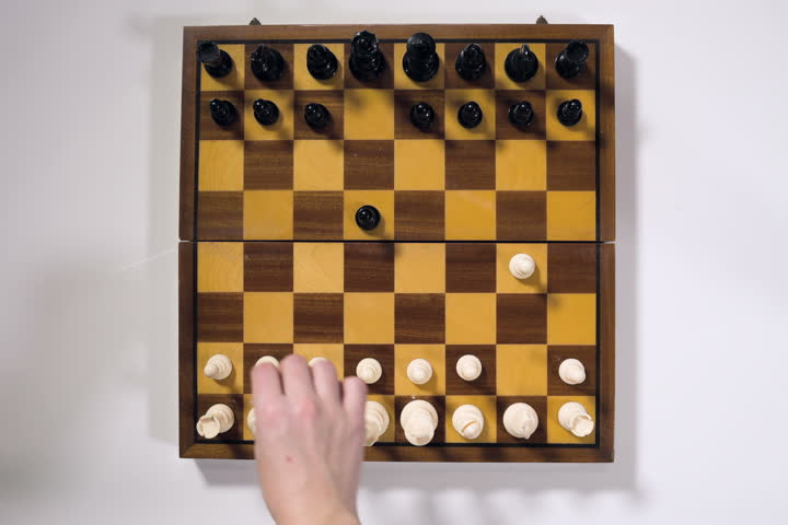 Time-lapse overhead view of male and female hands making the opening moves in a chess game.