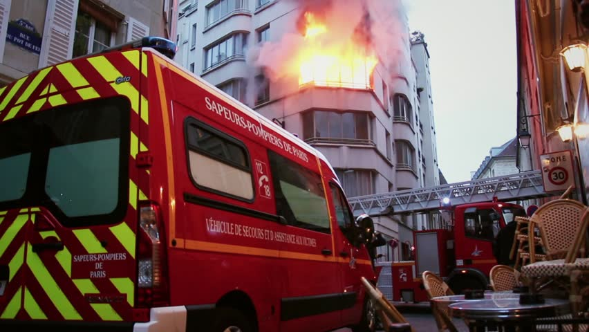 Fire Urgency in Central Paris with firefighters action. 4 OCTOBER 2015 - PARIS, FRANCE; An apartment explodes and catches fire, breaking all the windows and killing one person.