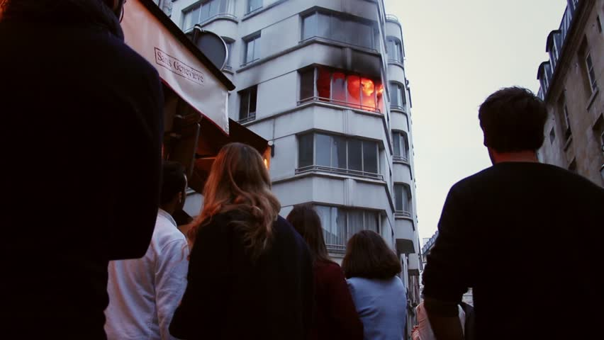 Crowd watches an apartment on fire. 4 OCTOBER 2015 - PARIS, FRANCE; An apartment explodes and catches fire, breaking all the windows and killing one person.
