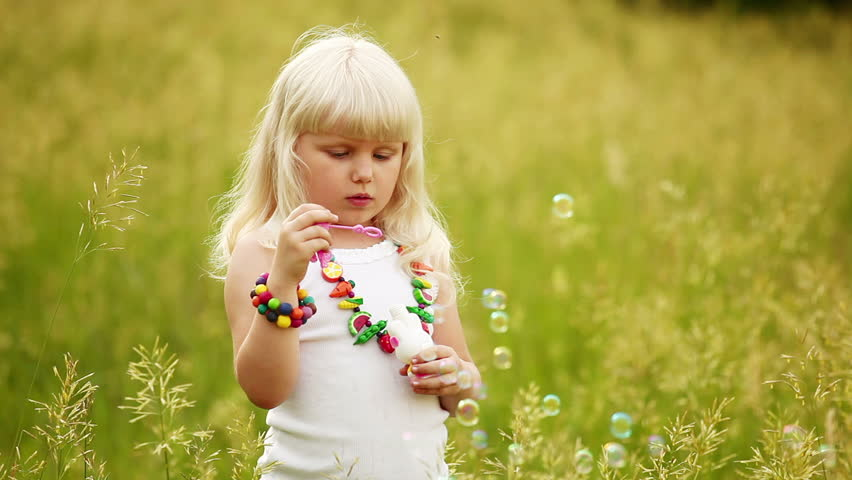 Child blowing bubbles. She laughs and look at camera.  - HD stock video clip