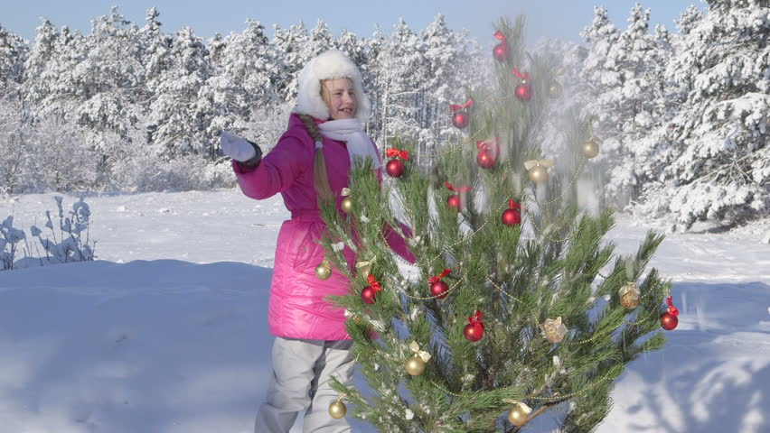 Child decorating Christmas tree in snow covered winter forest - HD stock footage clip