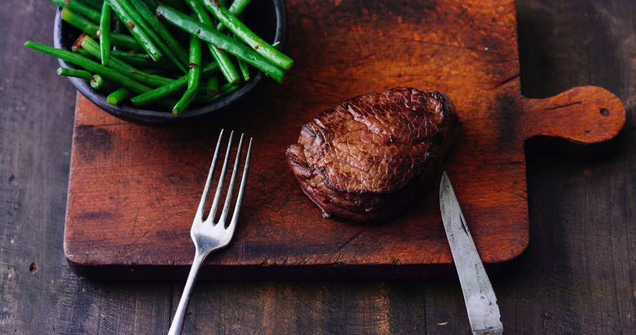 Cutting grilled piece of steak cooked medium rare - 4K stock footage clip