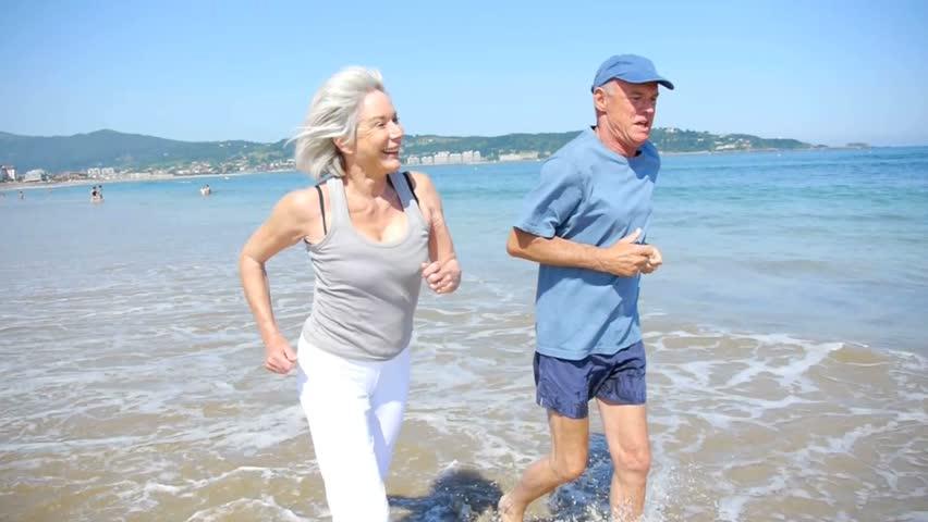 Senior couple jogging on a sandy beach - HD stock video clip
