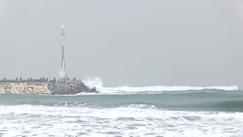 Lighthouse and high waves crushing rocks. lighthouse on background.