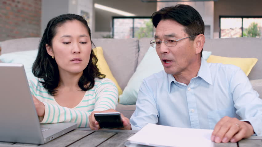 Concetrated couple calculating bills with laptop in living room - HD stock video clip