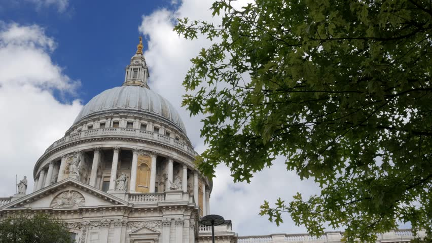 Static shot of the dome of St Pauls Cathedral in London framed by trees. White clouds and blue sky. Original footage is 4K - 4K stock video clip