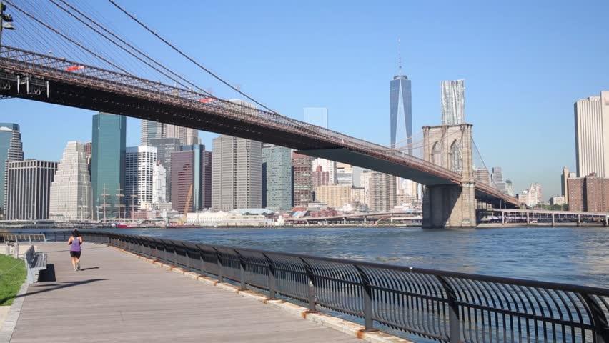 Skyscrapers, Brooklyn Bridge and unrecognizable woman runs in New York city