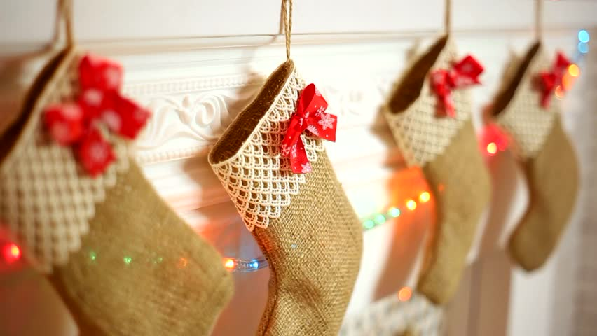 Close up of christmas stockings hanging on fireplace in for Stocking clips for fireplace