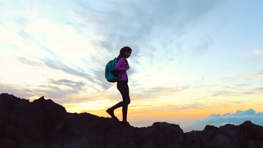 Hiker walks along narrow summit ridge crest at sunset. Reaching the Top. Young Woman Practicing Healthy Active Lifestyle.