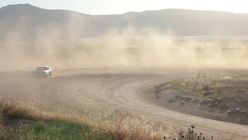 Race car crash on dirt oval course. Highly modified stock cars driving and racing on a very dirty and dusty track corner. High speed around dusty corner. - HD stock footage clip