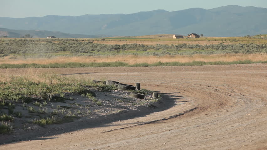 Race cars drive high speed on dirt oval course away from view. Highly modified stock cars driving and racing on a very dirty and dusty track corner. High speed around dusty corner.  - HD stock video clip