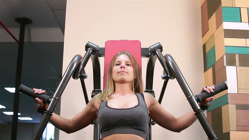 Bodyfitness workout. Athletic trainer for arms and back. Young woman doing exercises on athletic trainer in the gym