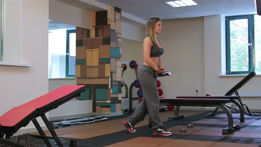 Bodyfitness workout. Exercises with dumbbells. Young woman doing exercises with dumbbells in the gym
