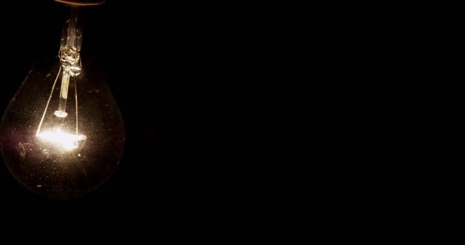 4K swinging filament lightbulb CU. Interrogation lighting. Shot with RED EPIC in 4K DCI Native Resolution UHD.