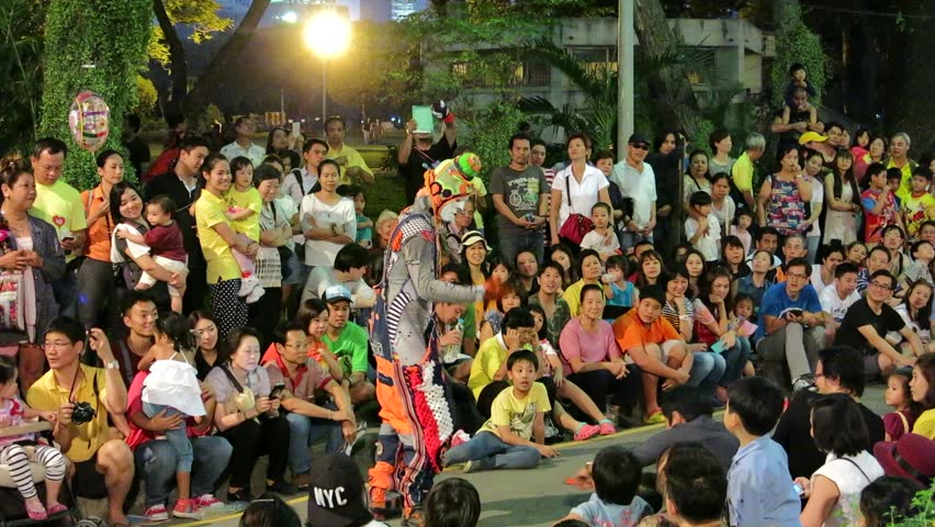 Bangkok, Thailand – December 14, 2014 – Street artists perform in the public Lumpini park to passerby. There are many people watch the performance.
