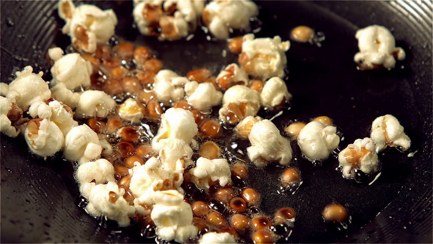 Popcorn popping in hot oil in slow motion - HD stock video clip