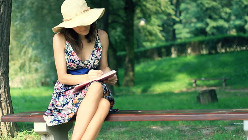 Young woman sitting on the bench in park with a diary  - HD stock video clip