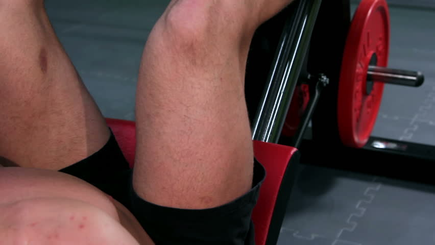 Workout for young bodybuilder. Man doing leg press with exercise equipment closeup