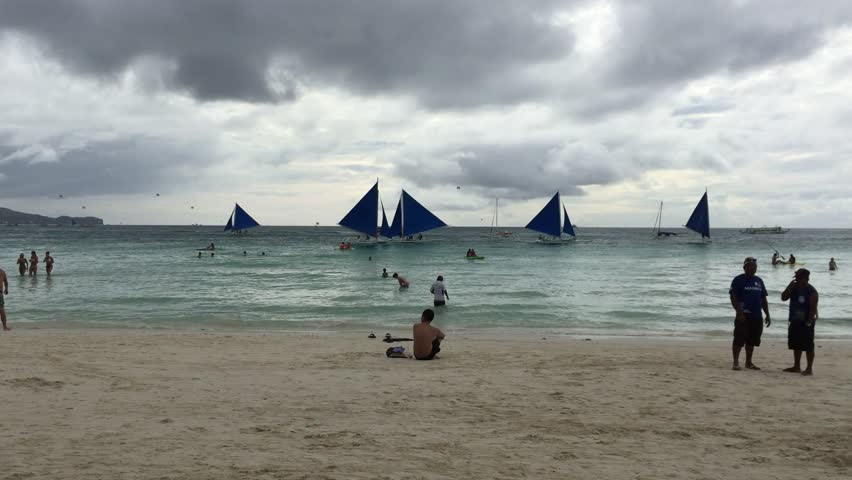 BORACAY, PHILIPPINES - MAY 5, 2015: Tourists walk on the tropical beach. Boracay is one of the main tourist attractions in the Philippines.