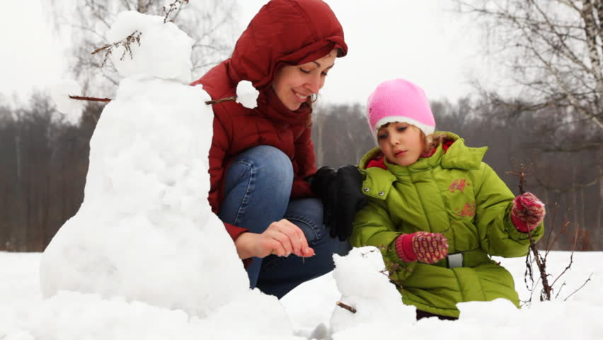 mother with cute little daughter make face for small snowman - HD stock video clip