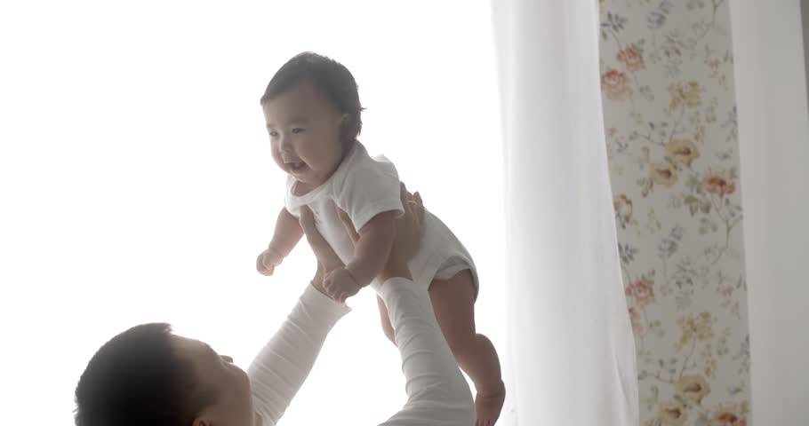 Young asian father lovingly holding up cute baby while they play together,slow motion