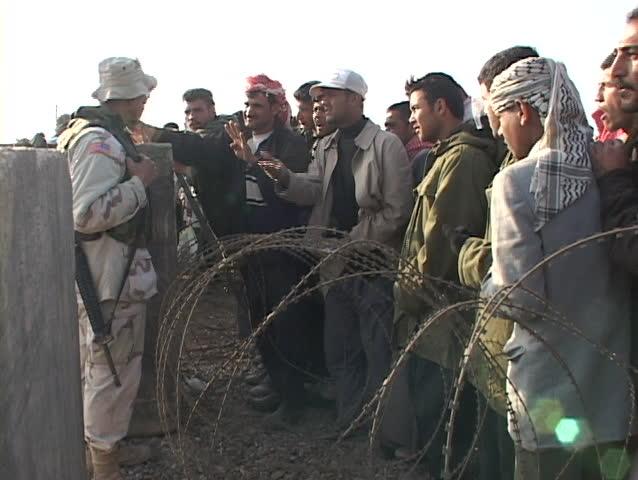 IRAQ - CIRCA 2003: U.S. soldier on a military base talks to Iraqi people waiting for work circa 2003 in Iraq.