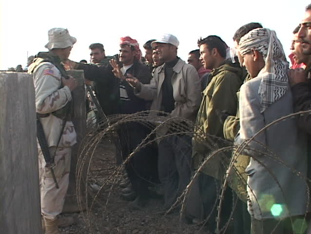 IRAQ - CIRCA 2003: U.S. soldier on a military base talks to Iraqi people waiting for work circa 2003 in Iraq.