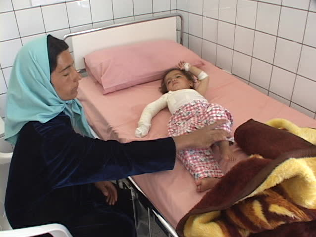 IRAQ - CIRCA 2003: An Iraqi mother tends to her injured baby in a hospital.The casualties of war circa 2003 in Iraq.