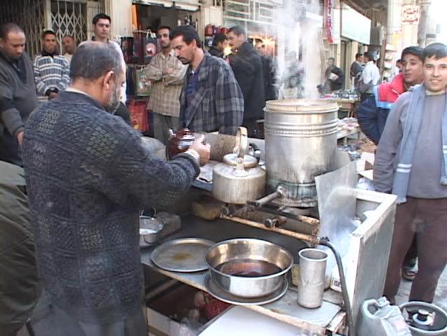 IRAQ - CIRCA 2003: An Iraqi street vendor serves hot tea as other Iraqi men watch circa 2003 in Iraq.