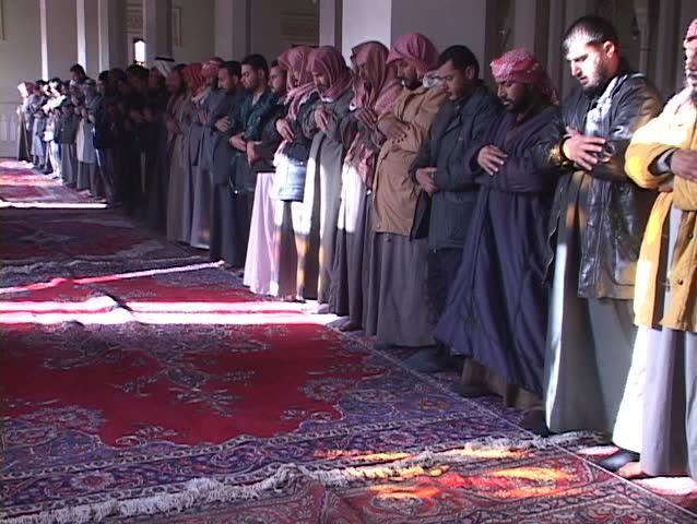 BAGHDAD, IRAQ - CIRCA 2003: Muslims pray in a mosque of war-torn circa 2003 in Baghdad, Iraq.