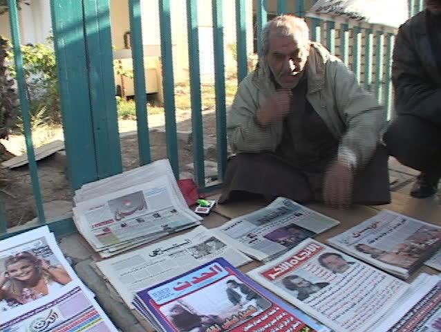 IRAQ - CIRCA 2003: An Iraqi vendor shows a newspaper with headlines of Saddam Hussein's capture circa 2003 Iraq.