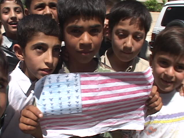 BAGHDAD - CIRCA 2003: An Iraqi boy holds up a drawing of the American flag circa 2003 in Baghdad.