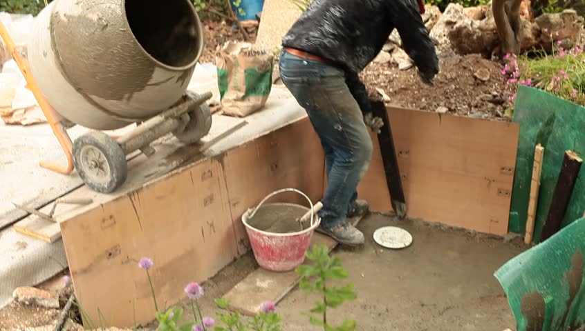 Artificial pond construction - mason sticking wood slat inside fresh cement in order to reinforce the wall of the basin.