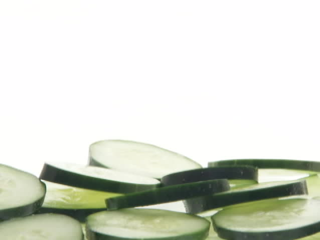 Slices of cucumbers fall into a pile..