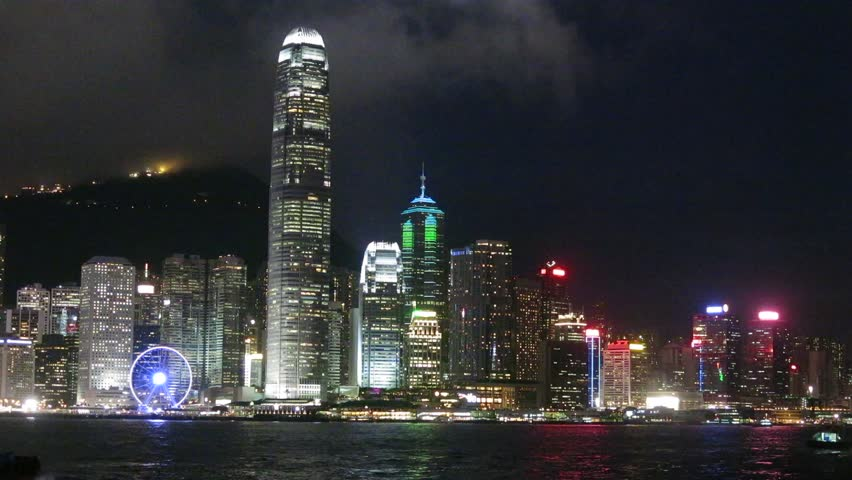 Light Display and skyscrapers in Victoria Harbour of Hong Kong. Boats are in the harbour.