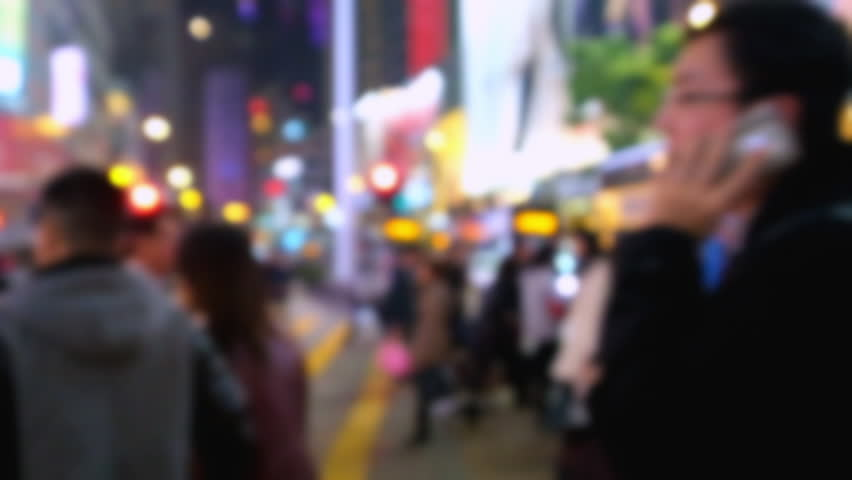 Blurred video of people moving at crossroad in crowded city street. Hong Kong night life