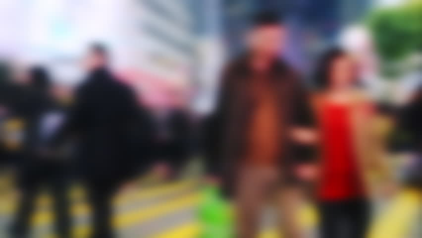 Blurred slow motion video of people moving at crossroad in crowded city street. Hong Kong night life