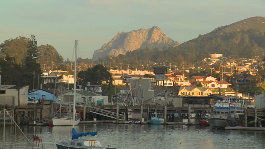 A pan across the small Central California town of Morro Bay with fishing boats in the harbor. - HD stock video clip