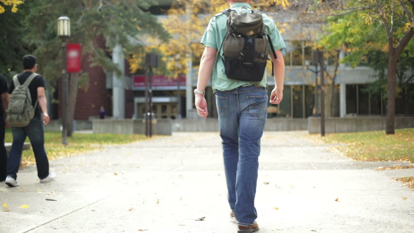 College student walking on a university campus.  - HD stock video clip