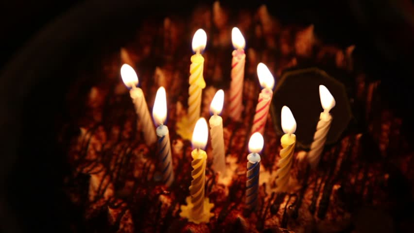 Happy Birthday cake with burning spiral candles which are then extinguished