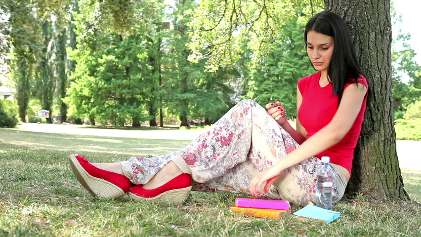 Beautiful girl reading a book outdoor and drink water  - HD video - HD stock footage clip