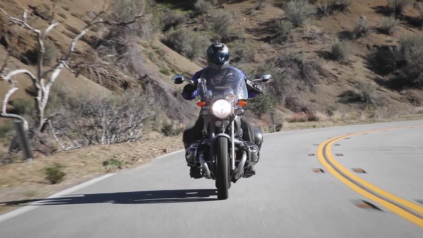 A man rides a motorcycle down a mountain road circa 2009 in Ojai. - HD stock footage clip
