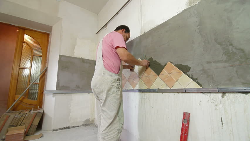 Man Setting Tile On Cement Board Side View Wide Angle
