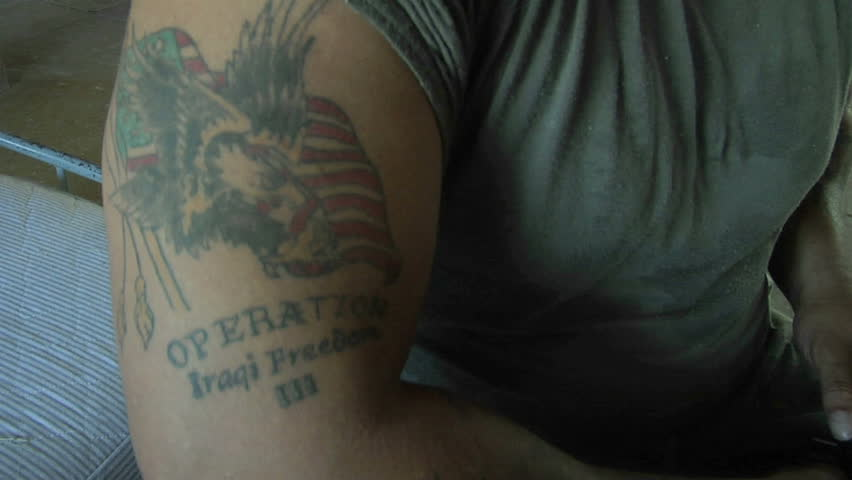 LOMPOC, CALIFORNIA - CIRCA 2010: A soldier's arm bares a tattoo of an American flag and bald eagle.