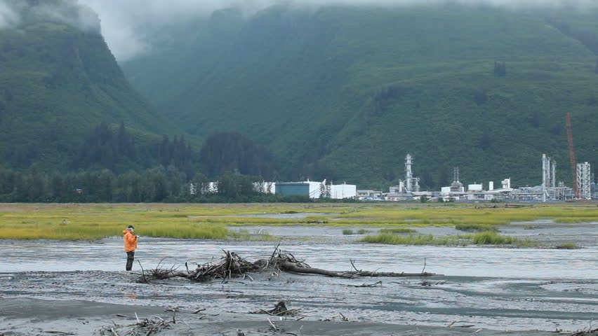 Man fishing for salmon in the rain and fog on a tidal river near oil refinery Valdez, Alaska.  - HD stock footage clip
